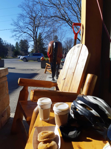 Donuts and coffee with a horse statue from behind and bike helmet