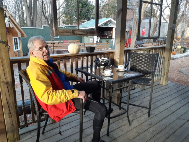 Man in cycling clothes sitting at an outdoor restaurant with coffee