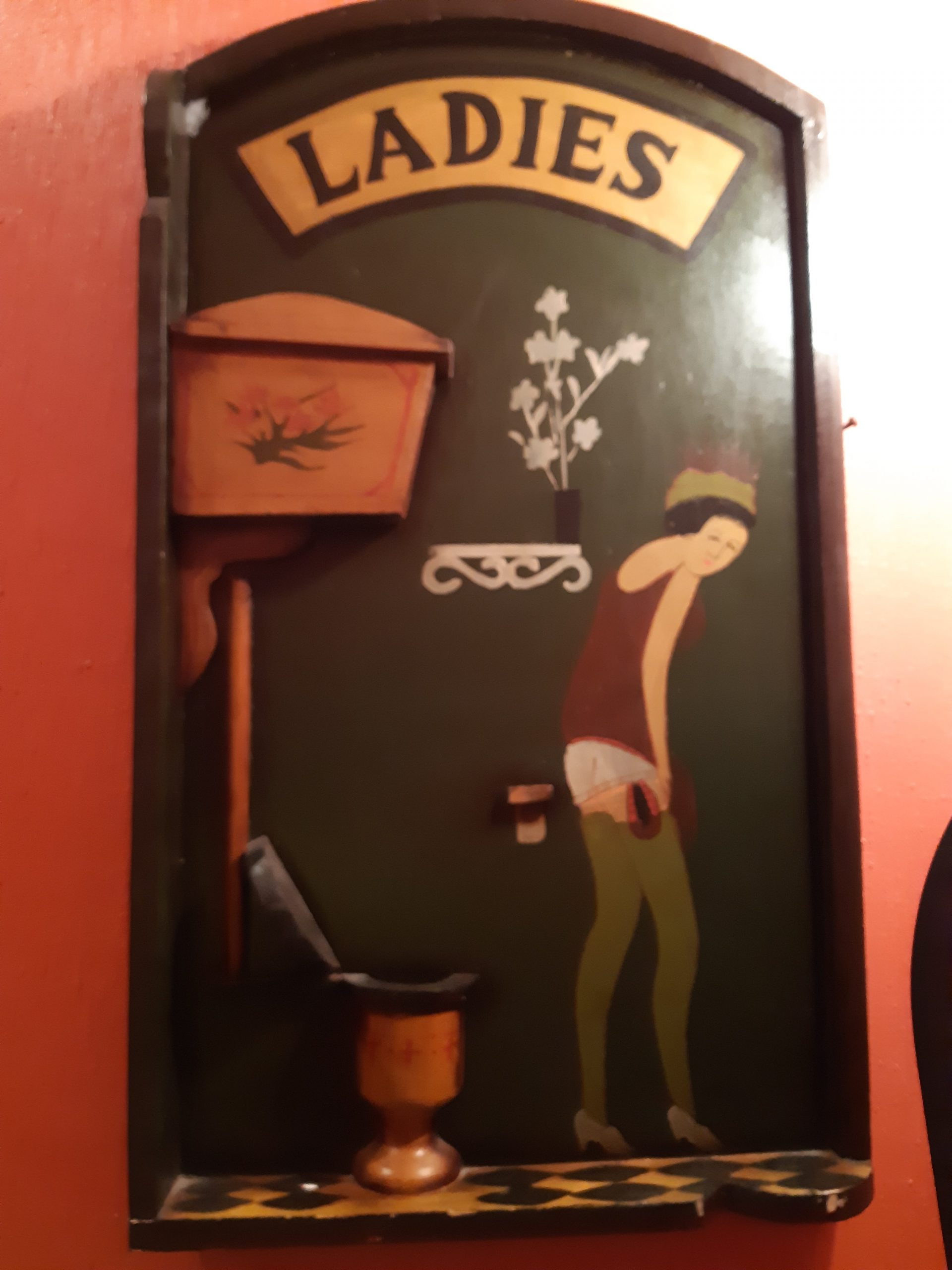 Painted sign in ladies washroom with ladie about to use old fashioned toilet