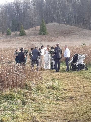 wedding party in a field with trees on hill in background
